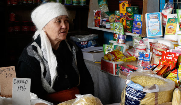 An elderly woman sells rice and other produce at the market in Talgar.