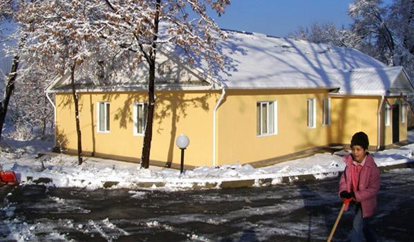 The 'peach' house, which is hosting children in daily service, on a snowy day.